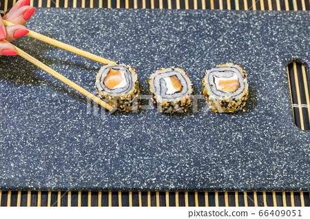 Woman using chopsticks for sushi eating 66409051