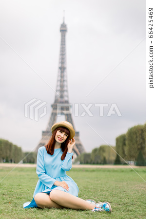 Elegant woman in straw hat and blue dress sitting on green grass in a park with Eiffel Tower on the background 66425469