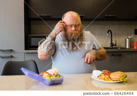 Tattooed adult big man looking thoughtfully at food 66426404