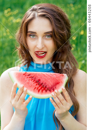 Woman holding watermelon. 66443208
