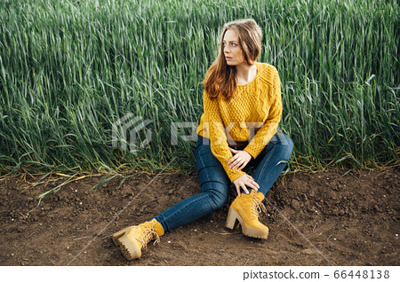 Beautiful girl with jeans, a yellow sweater and boots sits near an early wheat field 66448138
