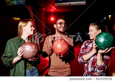 Happy young intercultural man with bowling ball talking to pretty girls 66449956