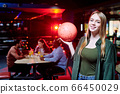 Happy young casual woman with long blond hair holding bowling ball 66450029