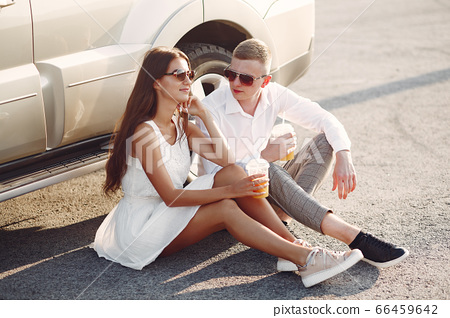 Beautiful couple spend time in a summer park near a car 66459642