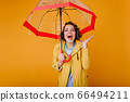 Attractive woman in yellow autumn coat expressing 66494211