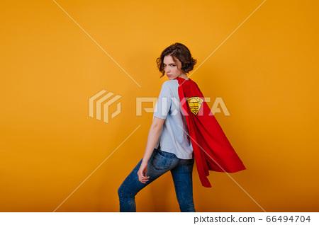 Playful girl in red cloak looking over shoulder 66494704