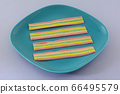 Chewy rainbow candy strips on blue dessert plate on lavender background 66495579