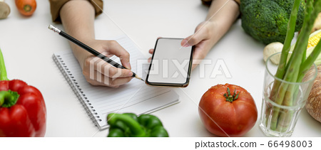 Female taking recipe notes on blank notebook while 66498003