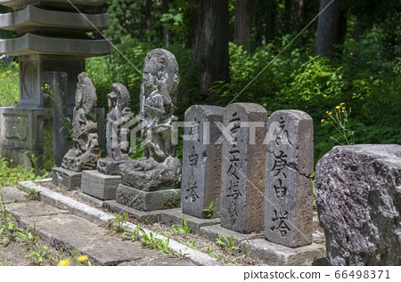 Stonework and stele with forest in the background 66498371