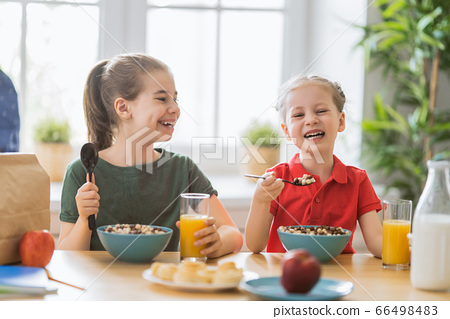 Happy children having breakfast. 66498483