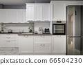 Electric appliances in minimalistic white kitchen interior 66504230