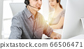 Casual dressed young man using headset and computer while talking with customers online in sunny office. Call center, business concept 66506471