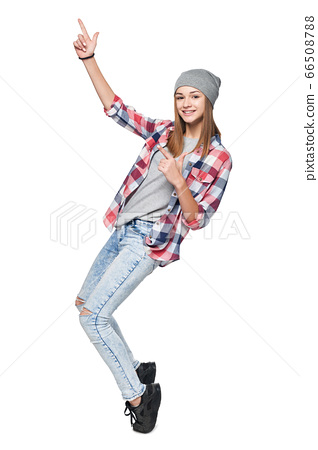 Teen girl standing in full length on tiptoe pointing to side at blank copy space 66508788