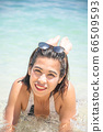 Portrait of Asian woman wearing white swimsuit and wear sunglasses lying on a sandy beach. 66509593