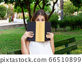 Young pretty girl is covering her face with a book 66510899