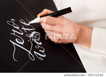 Woman writing on a small chalkboard zero waste 66512280