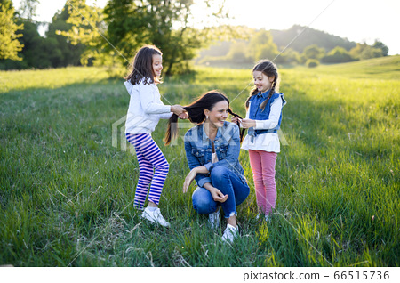 Mother with two small daughters having fun outdoors in spring nature. 66515736