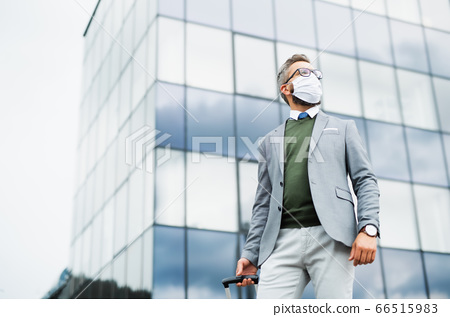 Businessman with luggage going on business trip, wearing face mask at the airport. 66515983