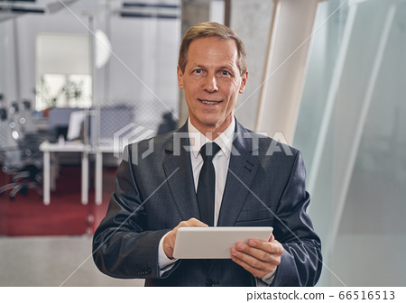 Cheerful man holding tablet in both hands 66516513