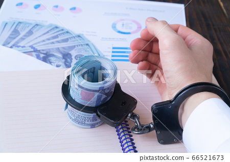 a man's hand in handcuffs, twisted dollars in handcuffs on the background of charts and money in an envelope 66521673