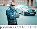 old modern man walks in the street, on the background of street and cars 66523178