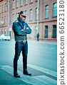 a man walks in the street, he has denim jacket, glasses, mustache and beard 66523180
