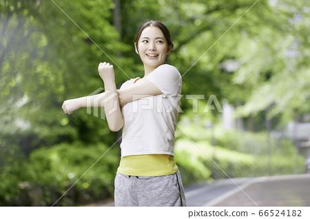 신록 속에서 스트레칭을하는 젊은 여성 66524182
