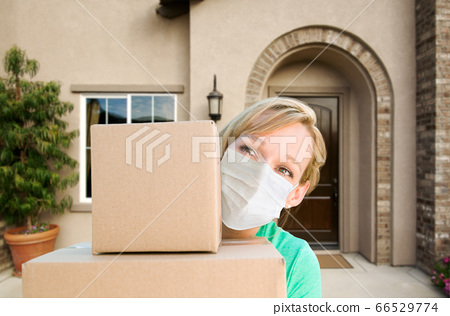 Female in Face Mask Holding Delivery or Moving Boxes At Front 66529774