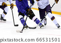 Ice hockey player dribbling puck on rink 66531501
