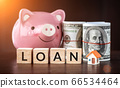 Real estate sale, savings, home loans market concept. model house with text loan on wooden cube, smilely pink Piggy bank and bank note 66534464