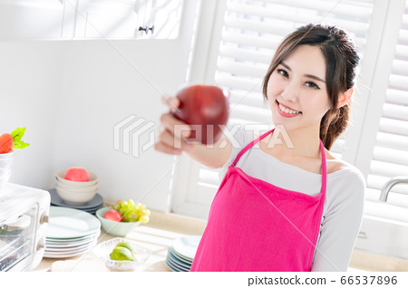 Asian housewife hold an apple 66537896
