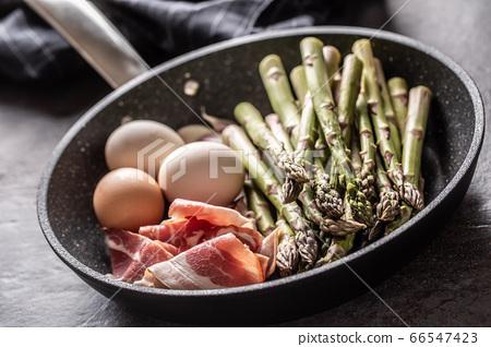 Asparagus eggs bacon and garlic in ceramic pan 66547423
