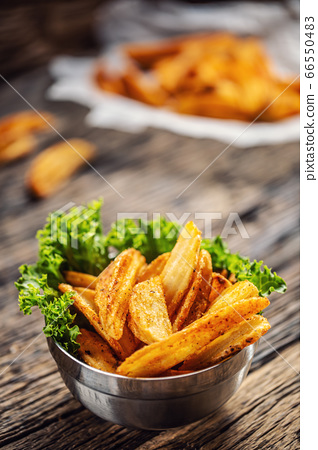 Crispy spiced potato wedges in a metal bowl with 66550483