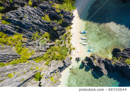 El Nido, Palawan, Philippines, top down bird eye aerial view of boats and cliffs rocky mountains scenery at Secret Lagoon beach 66550644