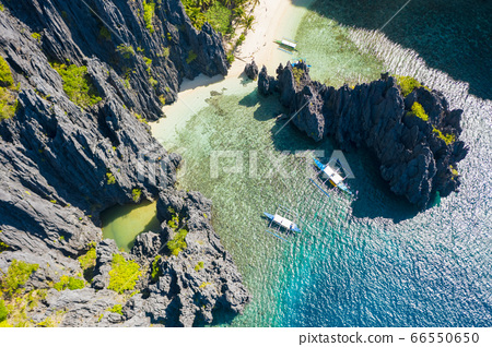 El Nido, Palawan, Philippines, aerial view of boats and cliffs rocky mountains scenery at Secret Lagoon beach 66550650
