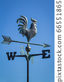 Weather vane showing direction of wind against clear blue sky, vertical 66551865