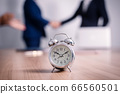 Alarm clock on  table with business people  in 66560501