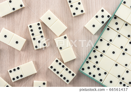 Playing dominoes on a wooden table 66561437