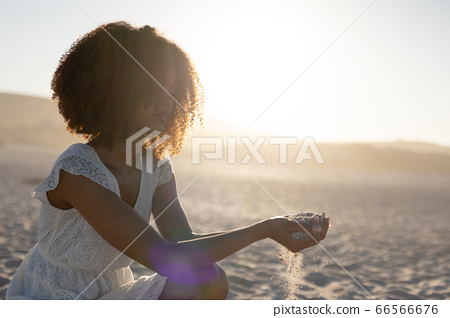 A mixed race woman enjoying free time on beach on a sunny day 66566676