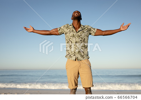 An African American man with his arms outstretched on beach on a sunny day 66566704