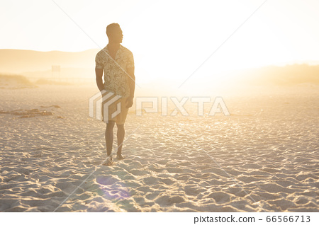 An African American man enjoying free time on beach on a sunny day 66566713