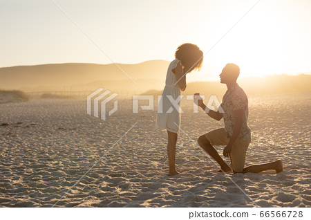 An African American man proposing to the woman on beach on a sunny day 66566728
