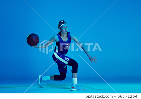 Young caucasian female basketball player isolated on blue studio background in neon light 66571264