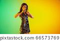 Caucasian female singer portrait isolated on gradient studio background in neon light 66573769