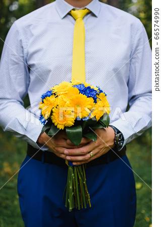 wedding bouquet in the hands of the groom 66574990