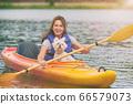 Woman and her dog on a kayak 66579073