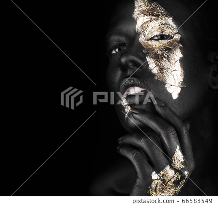 fashion portrait of a dark-skinned girl with gold make-up. Beauty face. 66583549