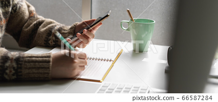Female university student noting on schedule book 66587284