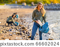 Smiling Young Female Volunteer holding bottle and garbage bag at beach 66602024