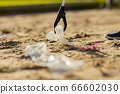Close-up up of volunteer picking up garbage with grabber at beach 66602030